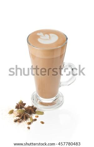 Modern supply masala tea. Masala tea in a glass for latte. Masala tea with latte art. spice cardamom, star anise, cloves and cinnamon. - stock photo