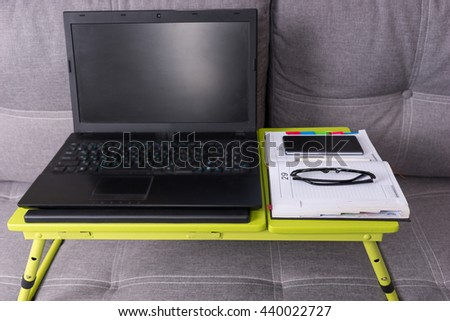 Modern tabletop workstation on a couch with laptop, stylish eyeglasses, a diary and mobile phone lying on it - stock photo