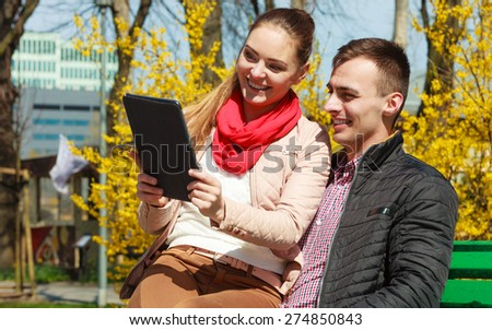 Modern technologies leisure and relationships concept. Young couple with pc computer tablet sitting on bench outdoor websurfing on internet - stock photo