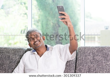 Modern technology, age and people concept. Indian mature man using smartphone selfie or self photographing. Asian living lifestyle at home. - stock photo