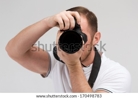 modern technology and people concept - male photographer taking picture with digital camera - stock photo