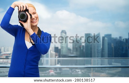 modern technology and people concept - smiling woman in casual clothes taking picture with digital camera over cityscape background - stock photo