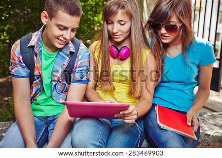 Modern teenagers with touchpad discussing homework after school - stock photo