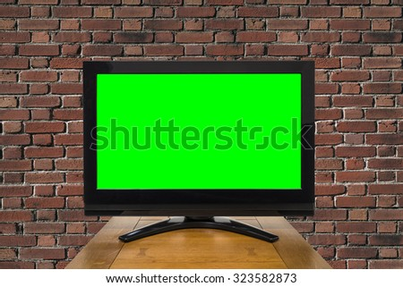 Modern television with chroma key green screen and red brick wall. - stock photo