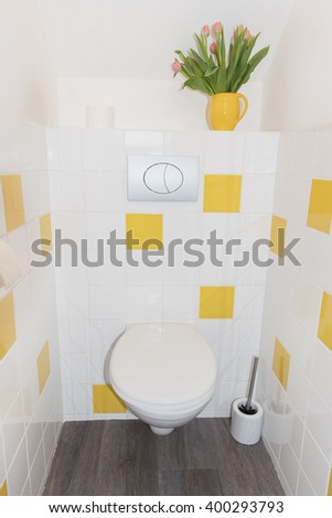 Modern toilet with yellow tiles - stock photo