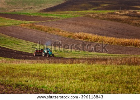 modern tractor in the agricultural field - stock photo