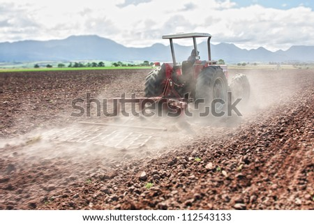 modern tractor plowing the soil in the farmland showing scraper - stock photo
