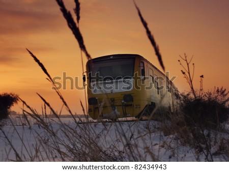 modern train at sunset in winter landscape - stock photo