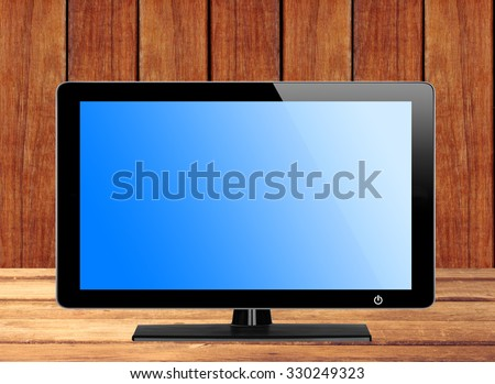 Modern TV screen with blue screen on wooden table - stock photo