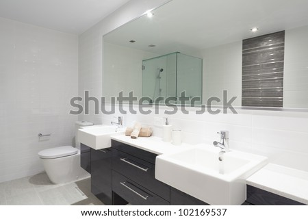 Modern twin bathroom with sinks, toilet and shower. - stock photo