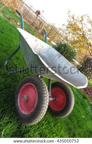 Modern two-wheeled wheelbarrow on the fresh lawn in the autumn garden - stock photo