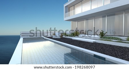 Modern upmarket home with huge glass windows , a patio and swimming pool overlooking the sea against a sunny blue sky - stock photo