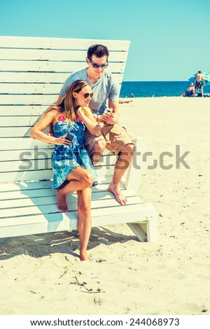 Modern Vacation. Wearing glasses, barefoot, dressing in summer outfits, girl and guy relying on each other on a wooden structure, reading messages on mobile phones. Young couple on the beach.  - stock photo