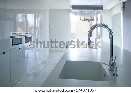 Modern white kitchen perspective with integrated bench sink and spring faucet - stock photo