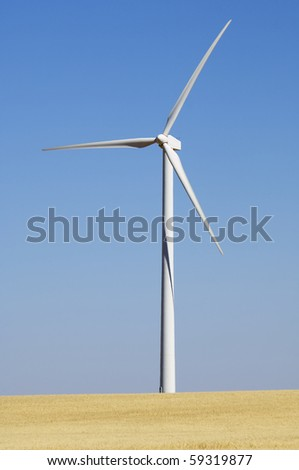 modern windmill in a field yellow with blue sky - stock photo