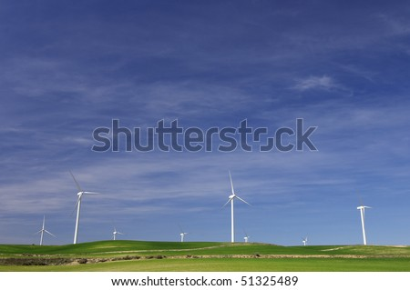 modern windmills looming in a green meadow - stock photo