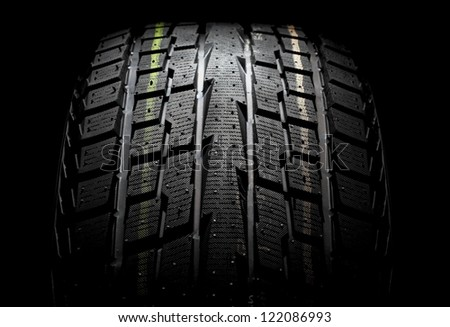 Modern winter performance tire for SUV. On a black background. - stock photo