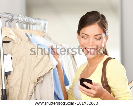 Modern woman shopping looking at smartphone texting or talking smiling happy in clothes store. Beautiful young mixed race Asian / Caucasian young woman shopper. - stock photo