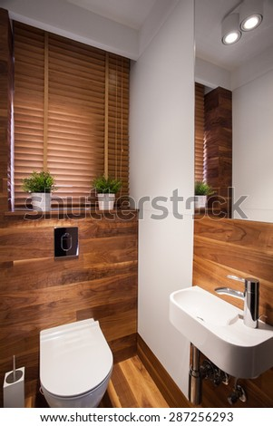 Modern wooden small restroom with little sink - stock photo