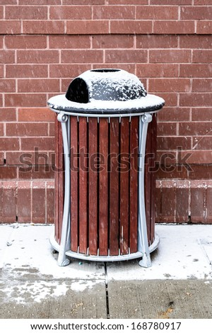 Modern wooden trash bin covered with snow - stock photo