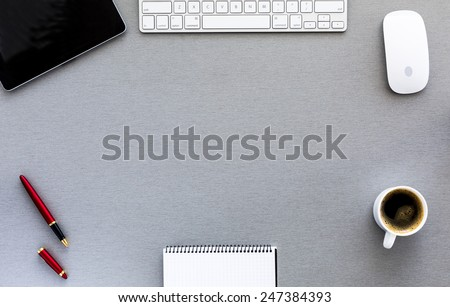 Modern working place on grey wood table. From above view on the well equipped working place surrounded with tablet PC, computer mouse and keyboard, red pen, blank notepad and cup of fresh coffee - stock photo