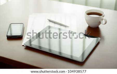 Modern workplace with digital tablet computer and mobile phone, cup of tea, pen and paper with numbers. - stock photo