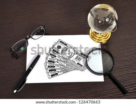 Modern workplace with drawing dollars on paper - stock photo