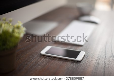 Modern workspace with a computer and a smartphone seen up close with a very shallow depth of field - stock photo