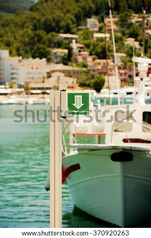 Modern yacht parked in harbor with beautiful defocused city behind - stock photo