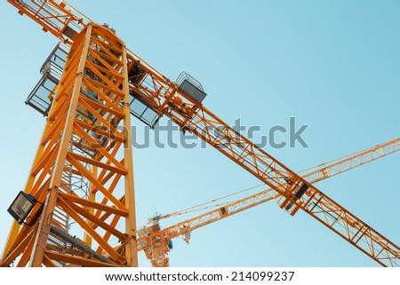 Modern yellow construction cranes above blue sky - stock photo