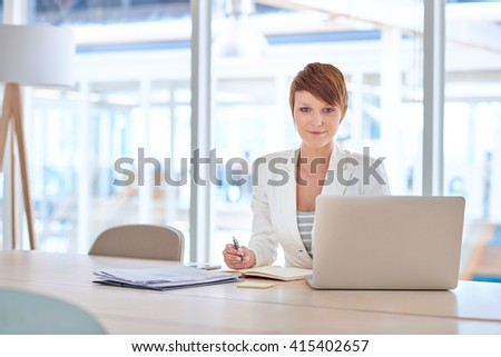 Modern young businesswoman at her desk in a bright office - stock photo