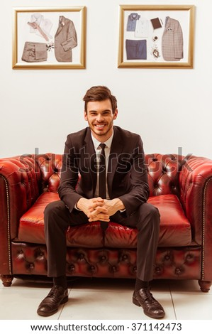 Modern young handsome businessman dressed in classical suit smiling while sitting on a sofa in the suit shop - stock photo