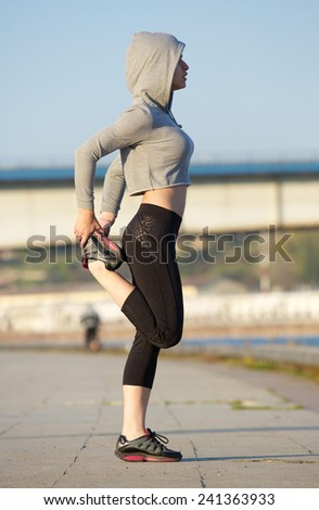 Modern young sports woman stretching leg muscles outdoors  - stock photo