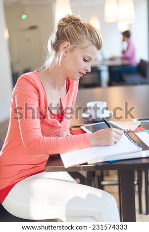 modern young woman sitting at a table in a cafe and writing on a paper - stock photo