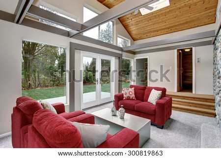 Modernized living room with red sofas, and large windows. - stock photo