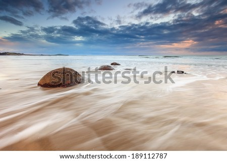 Moeraki Boulders beach, during cloudy sunrise with waves flowing over, South Island, New Zealand - stock photo