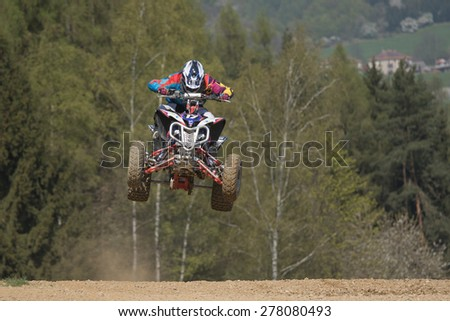 "MOHELNICE, CZECH REPUBLIC - APRIL 25. Juniorquad racer is jumping over the horizon in the ""International Championship of Czech Republic in Quad 2015"" on April 25. 2015 in Mohelnice. - stock photo"