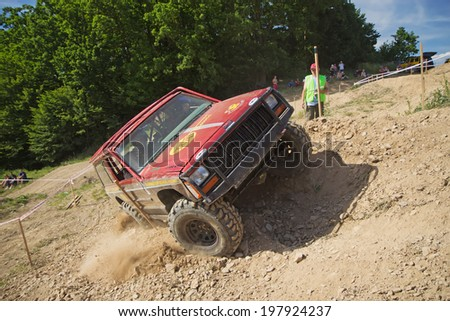 "MOHELNICE,  CZECH REPUBLIC - JUNE 07: Red offroad car is in lateral tilt. ""Championship of the Czech Republic in the off road tech trial-2014""  on June 07, 2014  in MOHELNICE, Czech Republic.  - stock photo"
