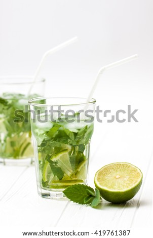 Mohito mojito drink with ice mint and lime on wooden white table. A glass with a refreshing drink - stock photo