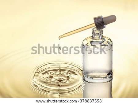 Moisturizing serum for dry skin stands in the water,  yellow background, pipette with drop, splash. - stock photo