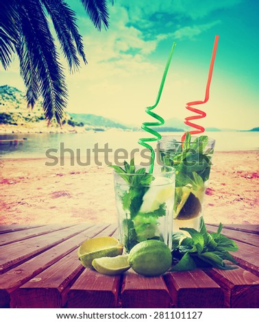 Mojito cocktail and beach in the background/ summer holiday background with two mojito cocktail - stock photo