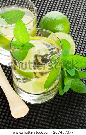Mojito cocktail and ingredients on black rubber mat - stock photo