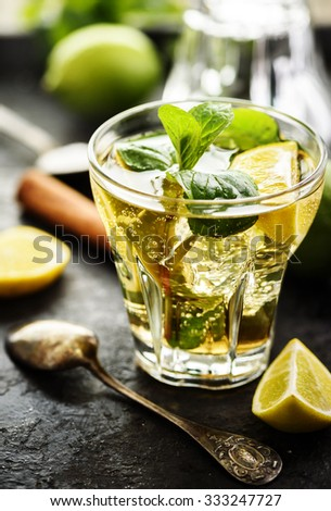 Mojito cocktail and ingredients on dark table  - stock photo