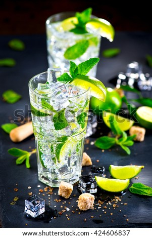 Mojito cocktail in a bur on a table in summer bar, Alcohol cocktails with Rum, lime, mint, ice cubes and brown sugar closeup, Party drink. Isolated on black background, selective focus - stock photo