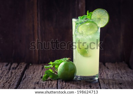 Mojito cocktail in a restaurant on a rustic wooden table - stock photo