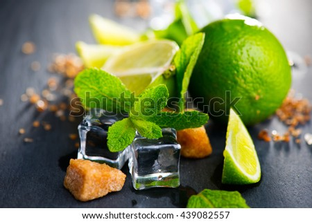 Mojito cocktail ingredients on a table in summer bar, Alcohol cocktails with Rum, lime, mint, ice cubes and brown sugar closeup, Party drink. Isolated on black background - stock photo