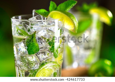 Mojito cocktail on a table in summer bar, Alcohol cocktails with Rum, lime, mint, ice cubes and brown sugar closeup, Party drink. Isolated on black background, selective focus - stock photo