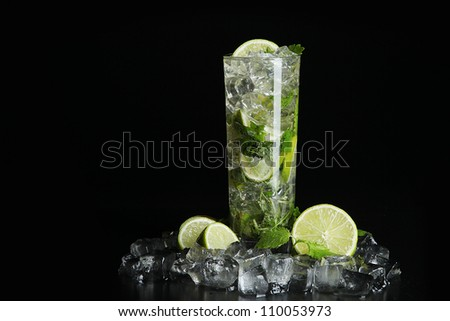 Mojito cocktail on black background with ice cubes - stock photo