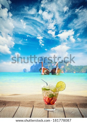 Mojito cocktail with fresh lime and strawberry at the beach  - stock photo