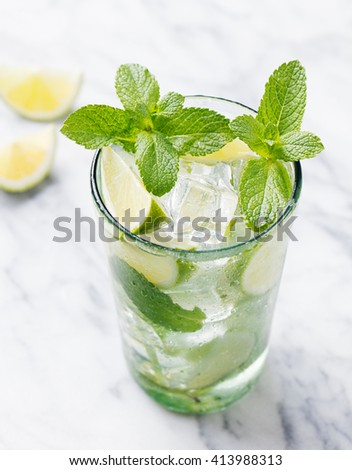 Mojito cocktail with lime and mint in highball glass on a marble table Blue background - stock photo